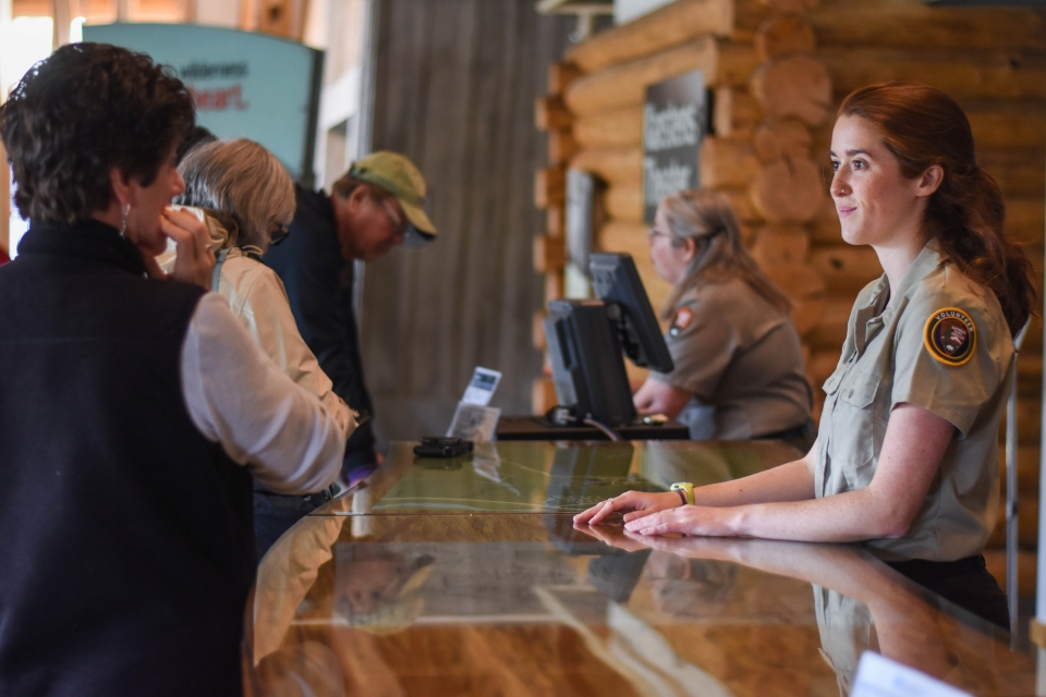 Two uniformed people at a desk speaking to visitors, Denali National Park and Preserve