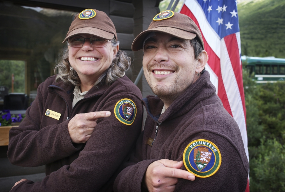 a man and woman in national park service volunteer uniforms smile and point to volunteer patches on their shoulders