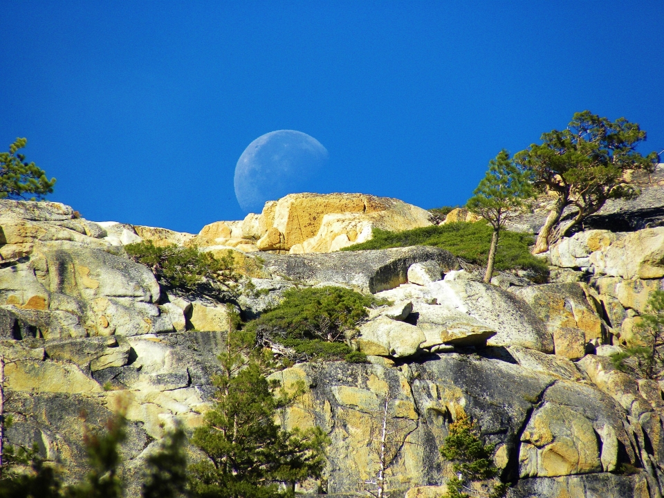 An outline of the moon shows through the bright blue sky over the cliffs of Devils Postpile National Monument.