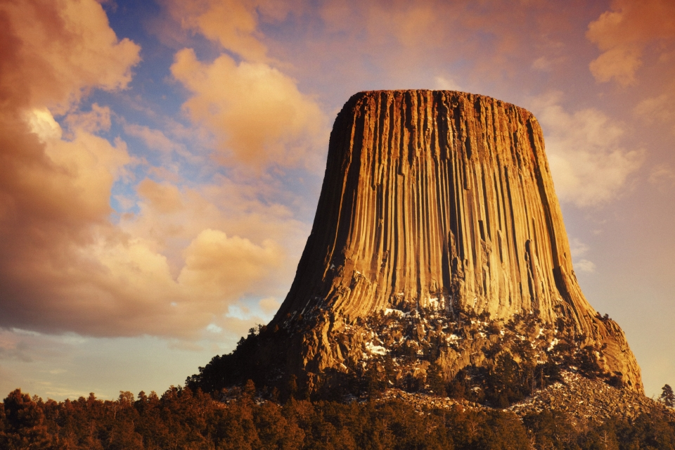 Towering monolith lit by the golden sunlight with pink and yellow clouds in the sky at Devil's Tower National Monument