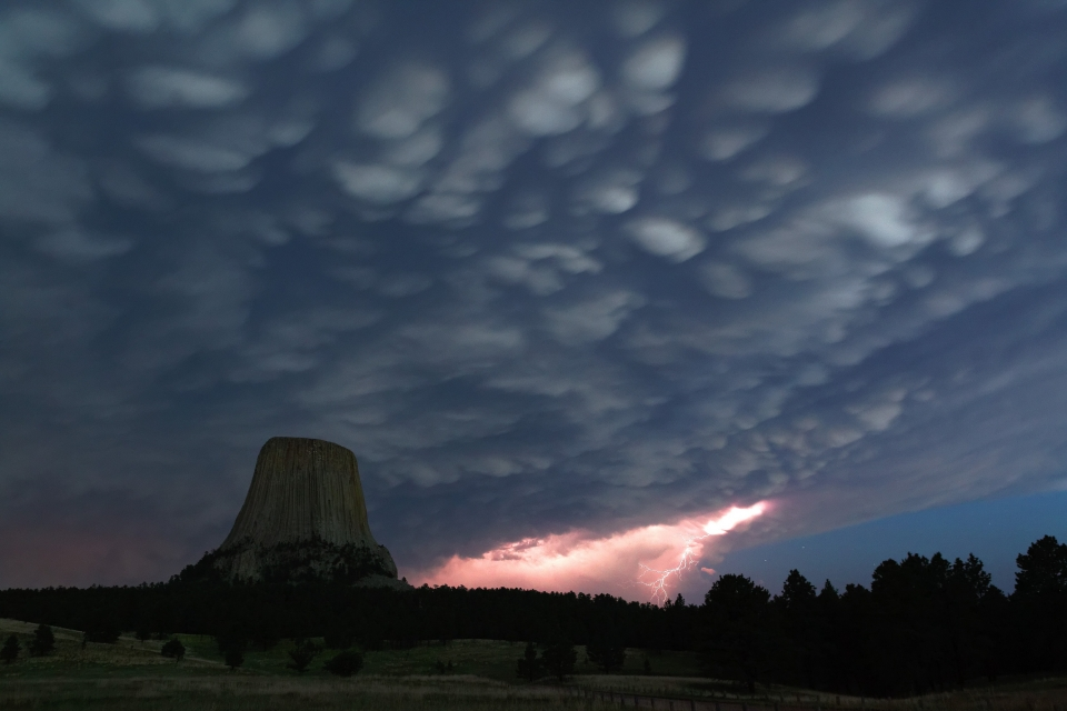 Heavily textured storm clouds over Devils Tower National Monument with a large lightning strike nearby