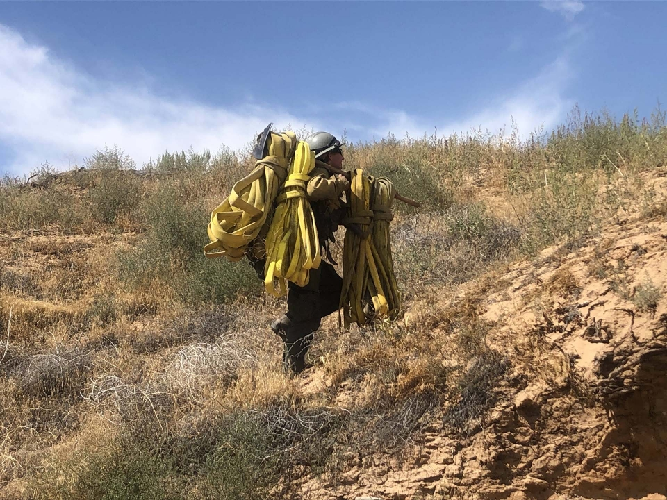 A woman treks uphill with a heavy firefighting hose slung over her shoulder