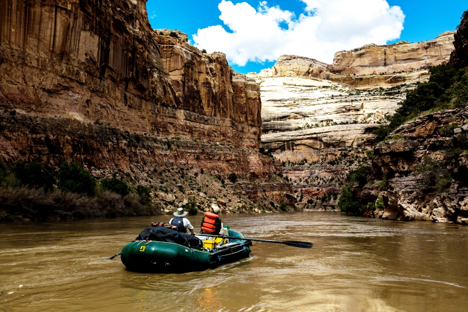 A lone raft flats down the Yampa River between high cliffs