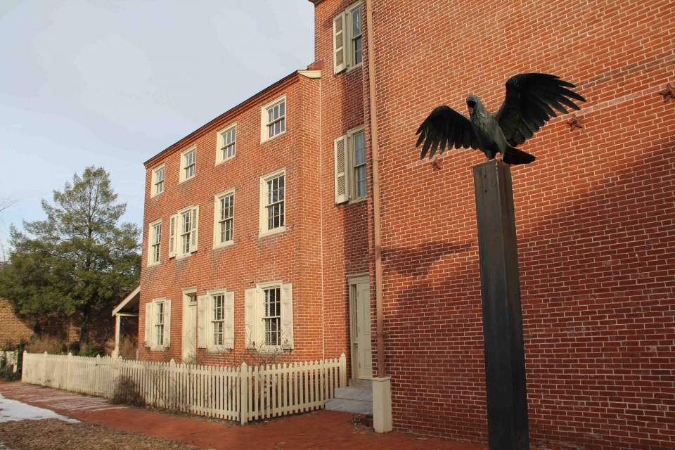 Black bronze statue of a crow outside the brick building at the Edgar Allan Poe National Historic Site