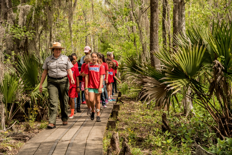 A group of 4th Graders walking on a wooden walkway at  Jean Lafitte National Historical Park & Preserve