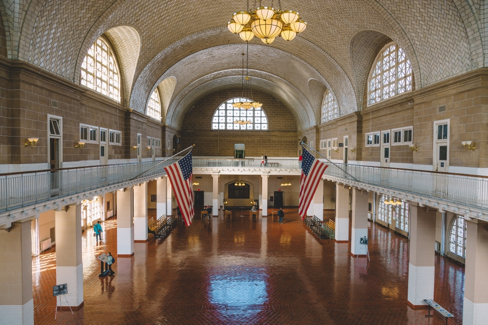 Large room with terra cotta-colored tile floor, a balcony, large arched windows, and creamy white tiled vaulted ceiling
