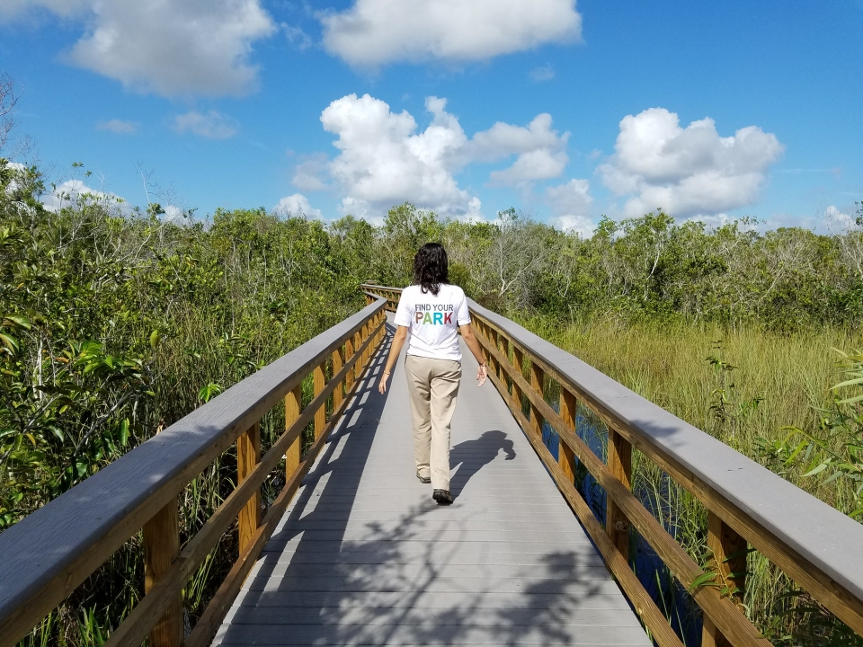 "A person in khaki pants and a white ""Find Your Park"" tshirt walks along a wooden boardwalk over green marshes on a bright sunny day"
