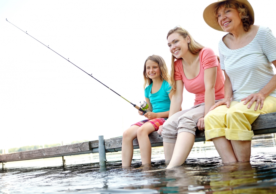 Three generations of family sit on a dock, fishing