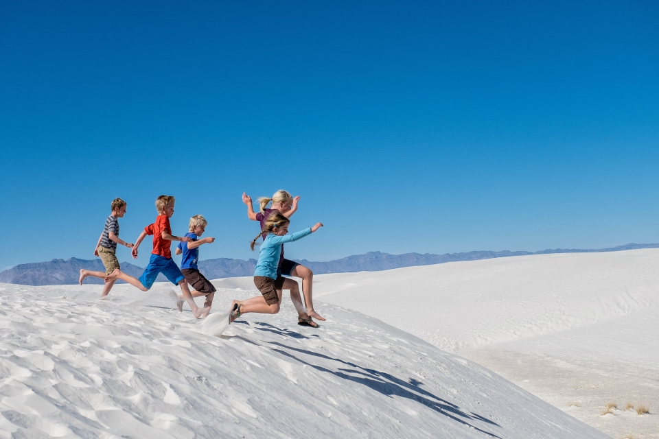 A group of children running barefoot through the white sand dunes at White Sands National Monument