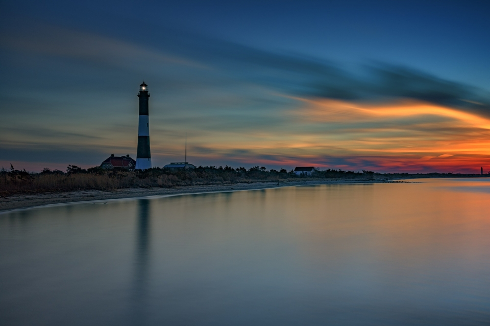 Striped lighthouse on the shore of Fire Island National Seashore during a colorful sunrise