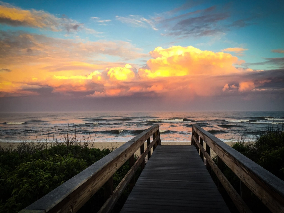 Below a multicolored sunset sky, a boardwalk at Watch Hill reaches the sand where waves gently roll in at Fire Island National Seashore.