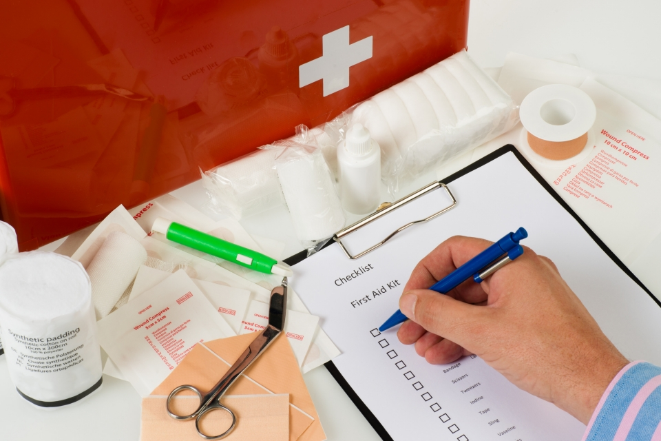 An unpacked first aid kit with a hand starting to go down a checklist for the First Aid Kit