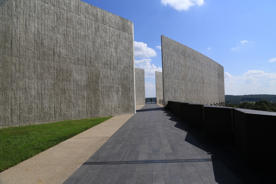 Tall gray concrete walls with gap and black walkway