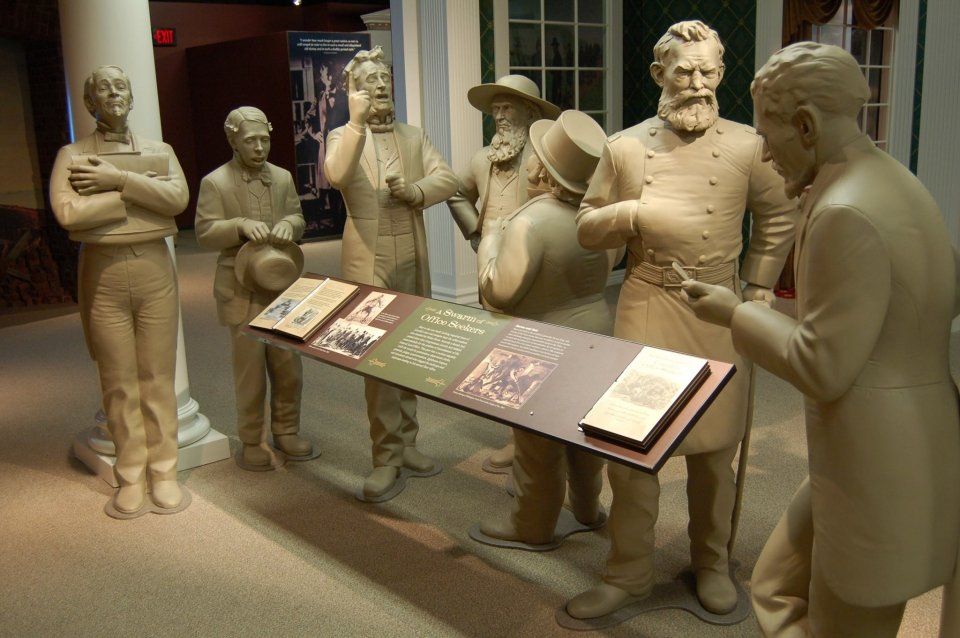 A display at the Ford's Theatre National Historic Site showing a statue of 7 men dressed in colonial era dress talking amongst themselves