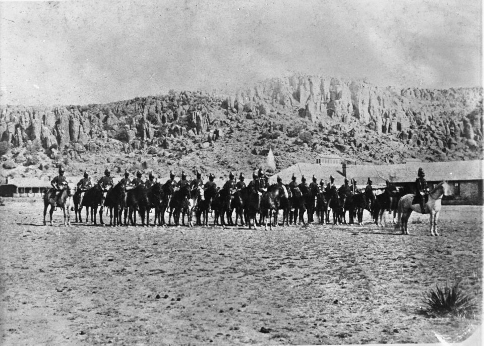 Black and white image of the 9th US Cavalry Company I at Fort Davis National Historic Site in Texas in dress uniforms on their horses in a line in front of cliffs in the background