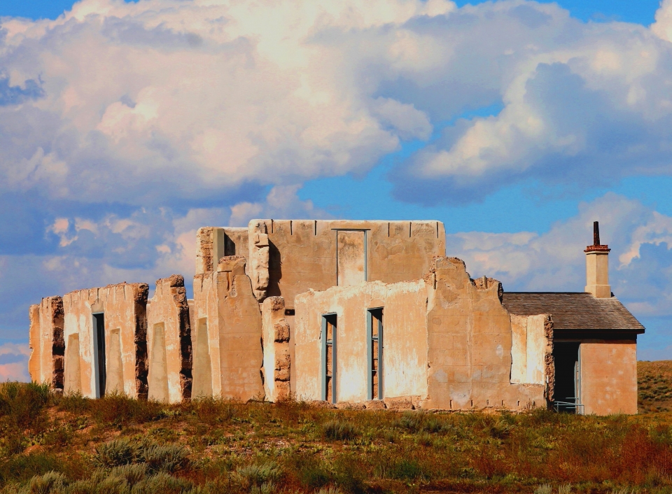 White clouds in a blue sky over the orange concrete remnants of Fort Laramie National Historic Site