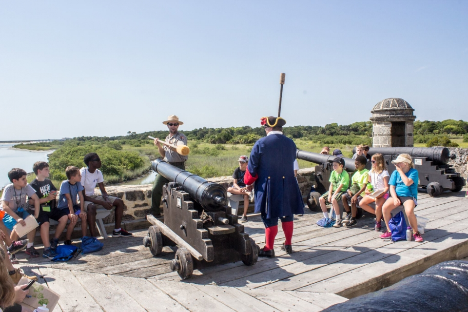 Historical actor and a National Park Service ranger showing students how canons were loaded at Fort Matanzas National Monument