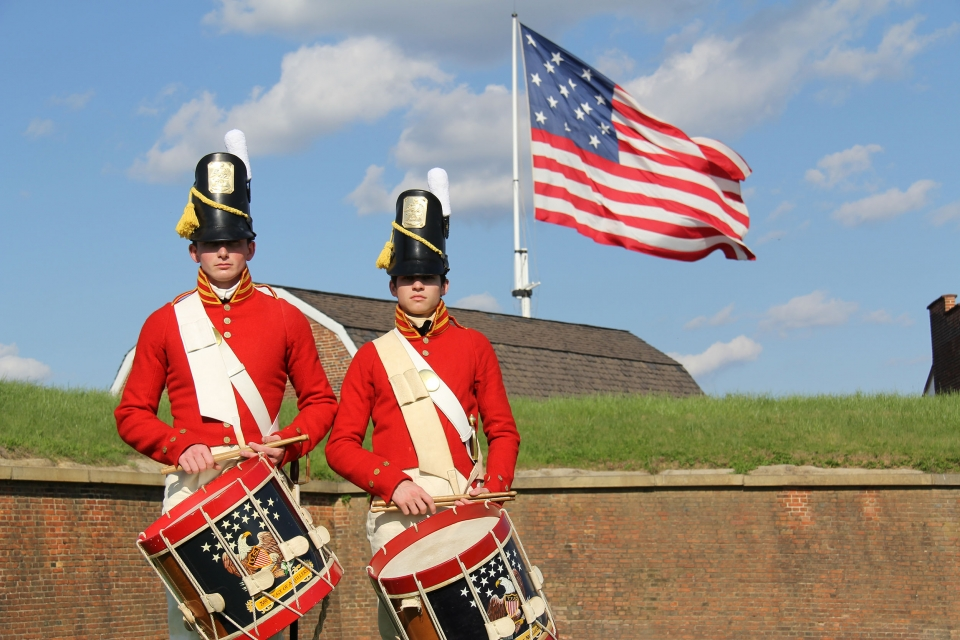 Drummers in full military regalia in front of the American flag