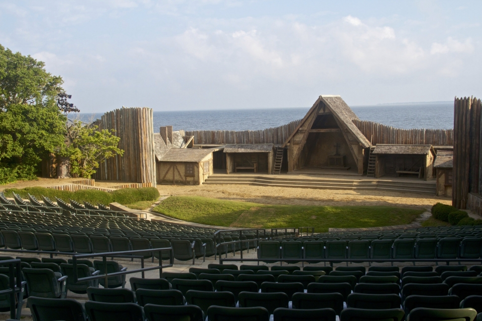 Softly lit wooden Waterside Theatre with the Roanoke Sound in the back at Fort Raleigh National Historic Site