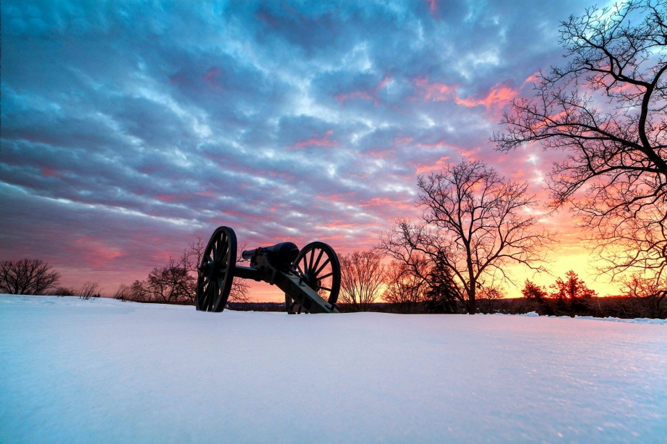 Canon in the snow with a colorful blue, pink, and yellow sunset in the horizon