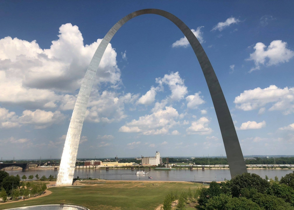 A view of the towering metallic arch of Gateway Arch National Park on a sunny day looking out towards the Mississippi River