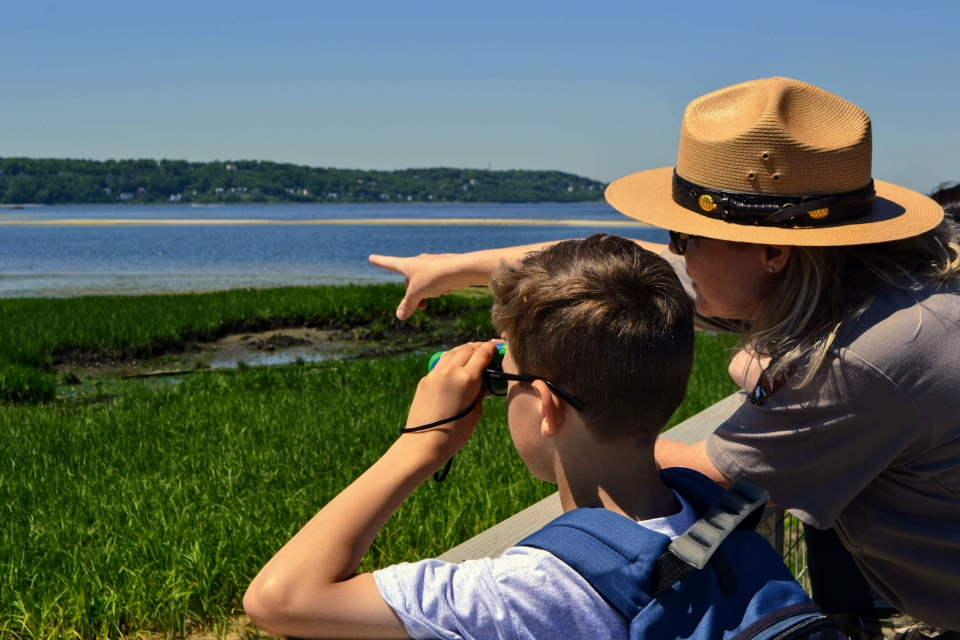 A park ranger and student birdwatching at Gateway National Recreation Area