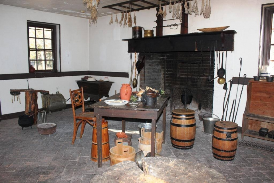 A colonial kitchen with a fireplace for cooking and a wooden table and wooden barrels at George Washington Birthplace National Monument
