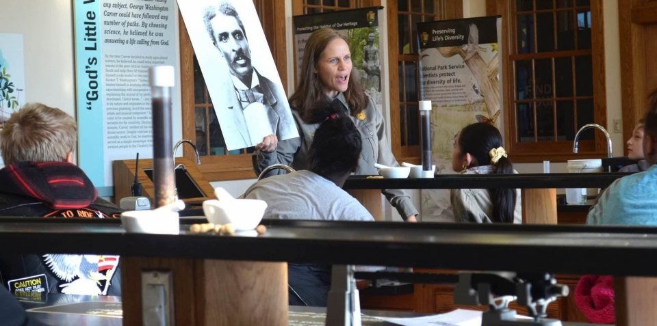 A park ranger holding up a poster of George Washington Carver in a lab classroom at George Washington Carver National Monument
