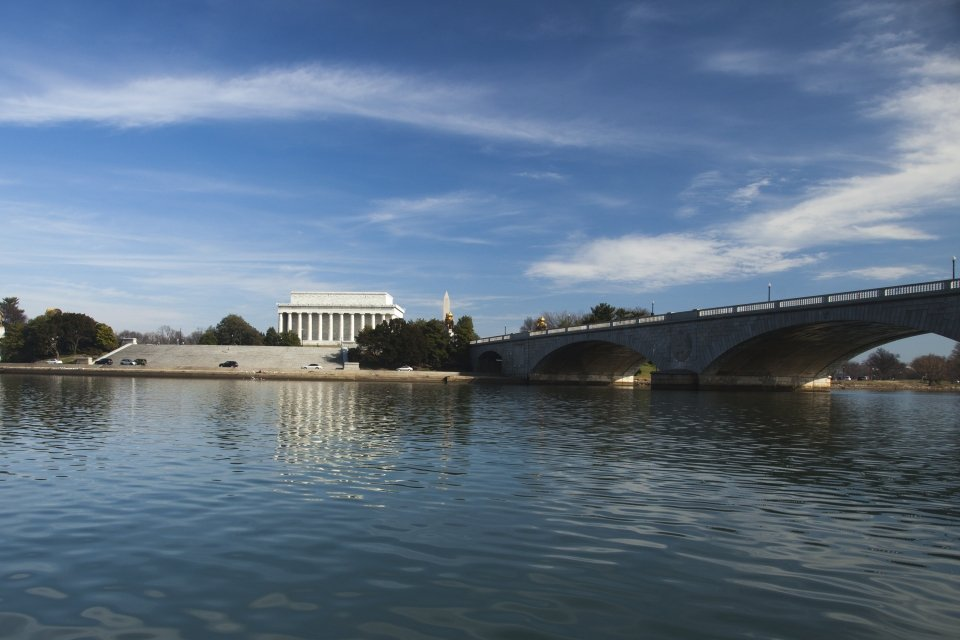 The George Washington Memorial Parkway Bridge over the Potomac River leading toward the white Lincoln Memorial on a sunny day in Washington DC