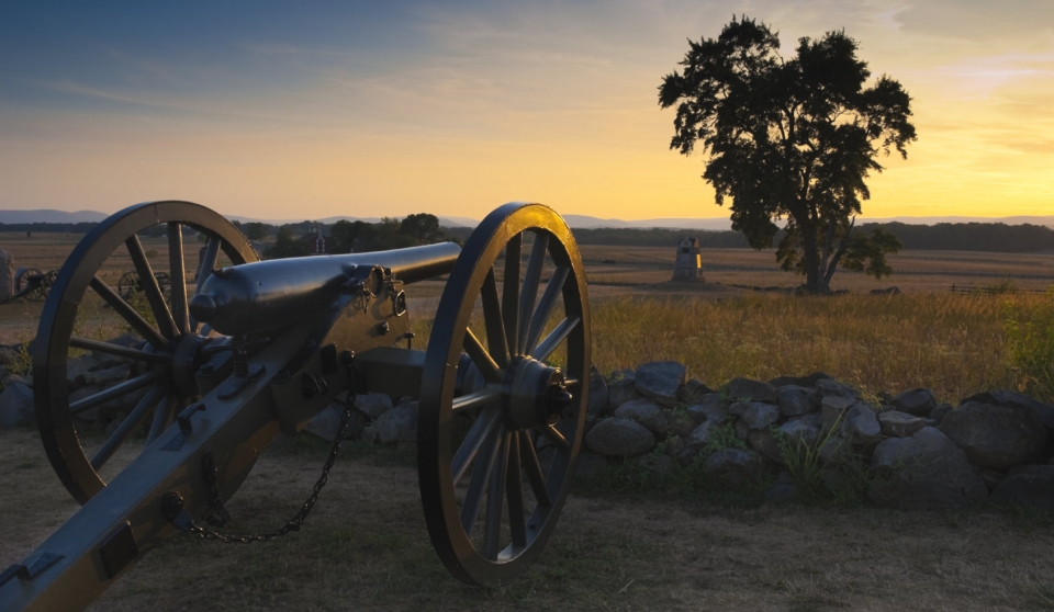A canon pointing out over a rock wall towards the sunset at Gettysburg National Battlefield