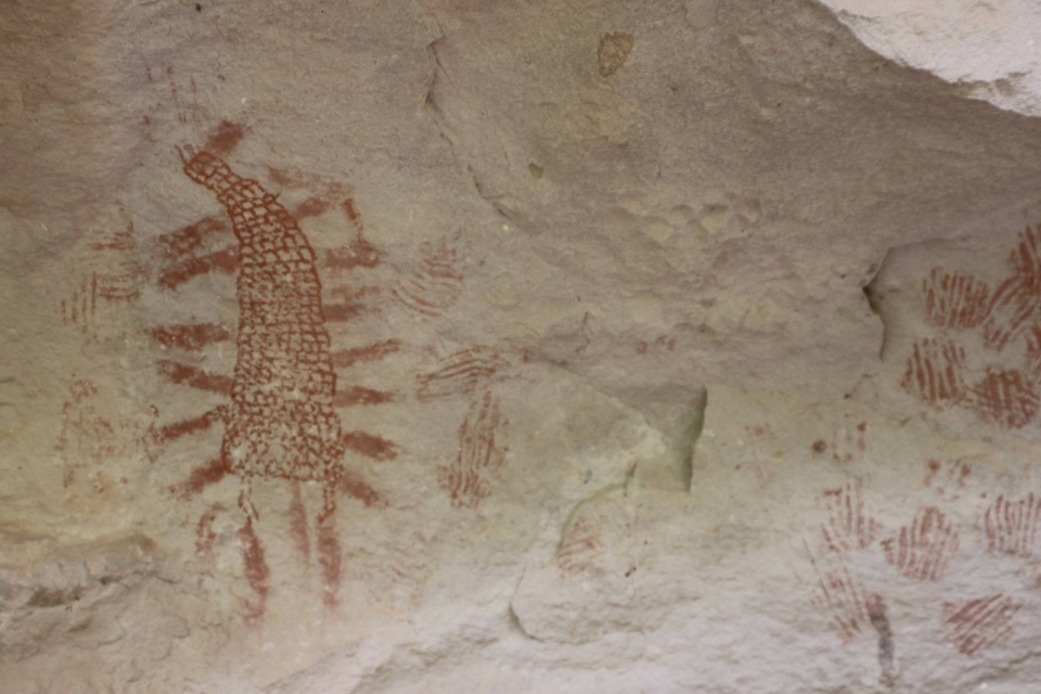 Red painted pictographs on a tan stone wall at Gila Cliff Dwellings National Monument
