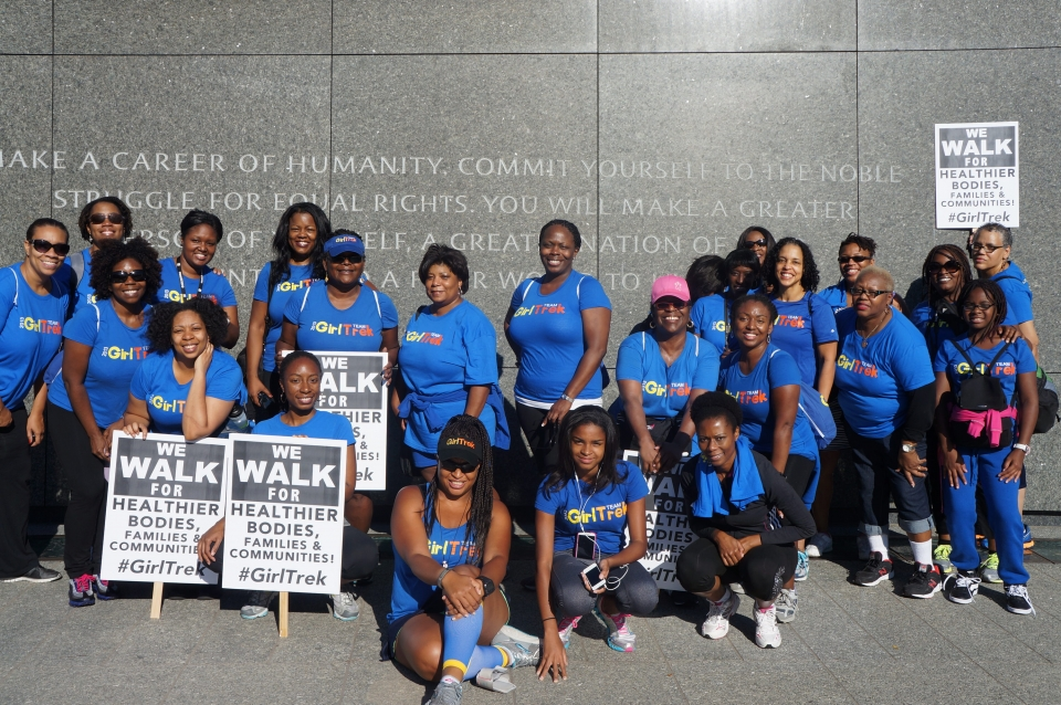 "Large group of women standing in front of an inscribed wall in Washington DC holding signs that say ""WE WALK FOR HEALTHIER BODIES, FAMILIES & COMMUNITIES #GIRLTREK"""