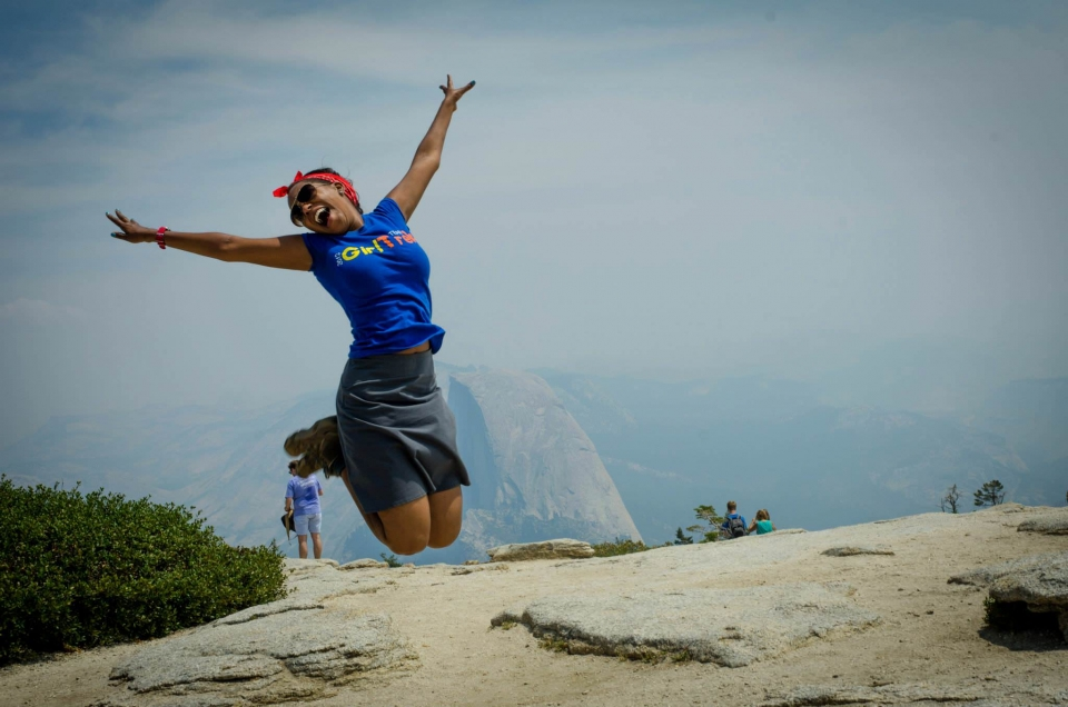 African American woman wearing a GirlTrek shirt jumping with Yosemite's Half Dome in the background