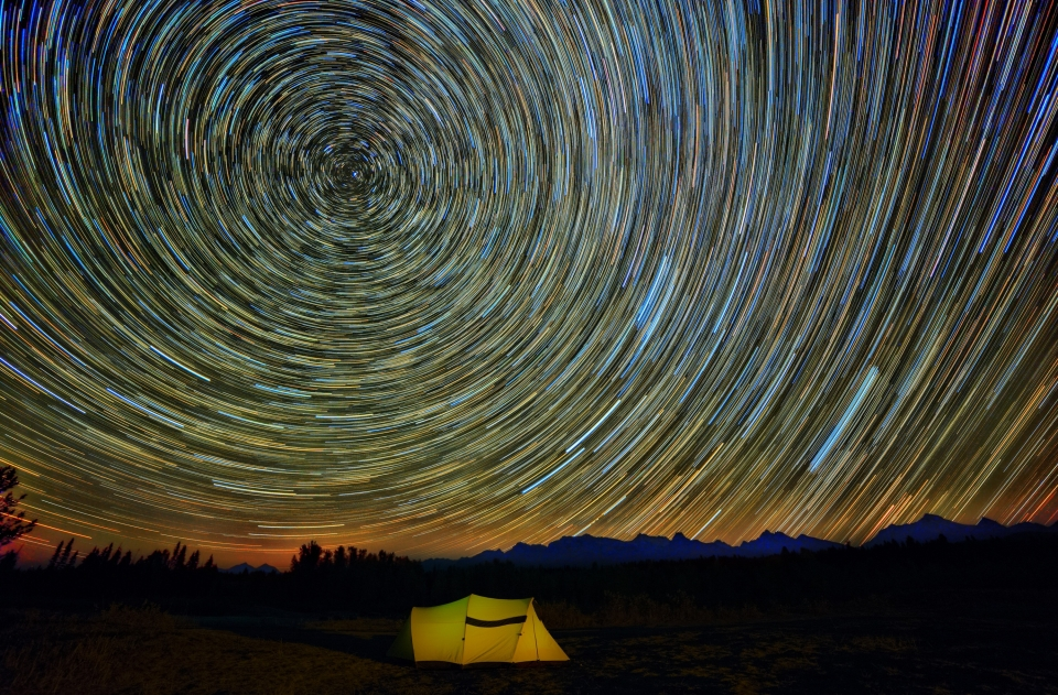 A lighted tent sits beneath a colorful spiral star effect at Glacier National Park
