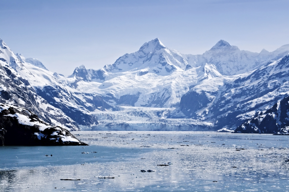 The snow and glacier-covered mountains behind a blue bay at Glacier Bay National Park