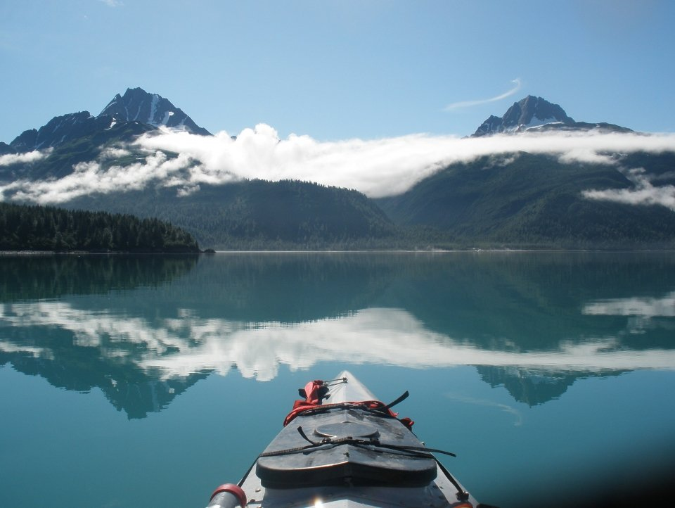 Kayak on still water. Ahead is a range of snow-capped mountains, with clouds wafting around them