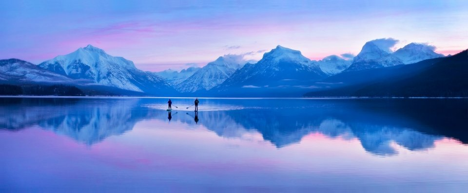 Two people paddle board at Glacier National Park's Lake McDonald
