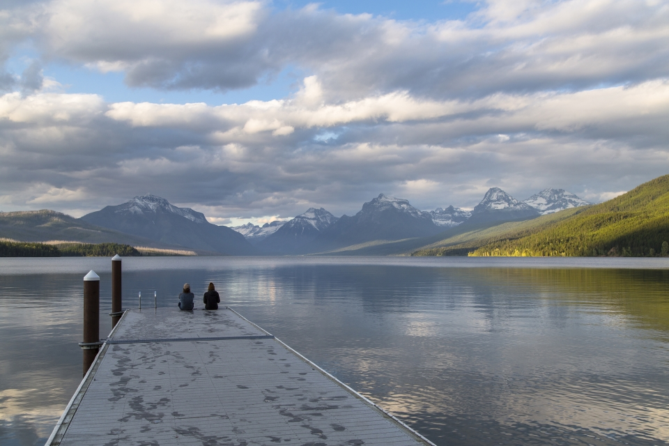 Two people sit at end of dock, facing lakes and mountain range