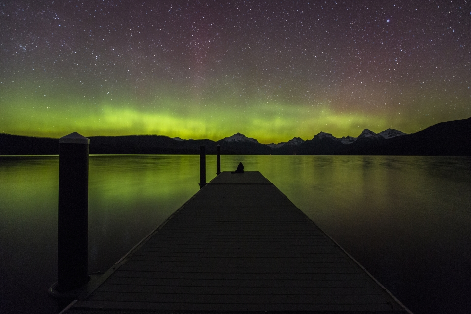 Green northern lights dance across the night sky, illuminating the mountain range and water below. A dark dock stretches into the mid-distance