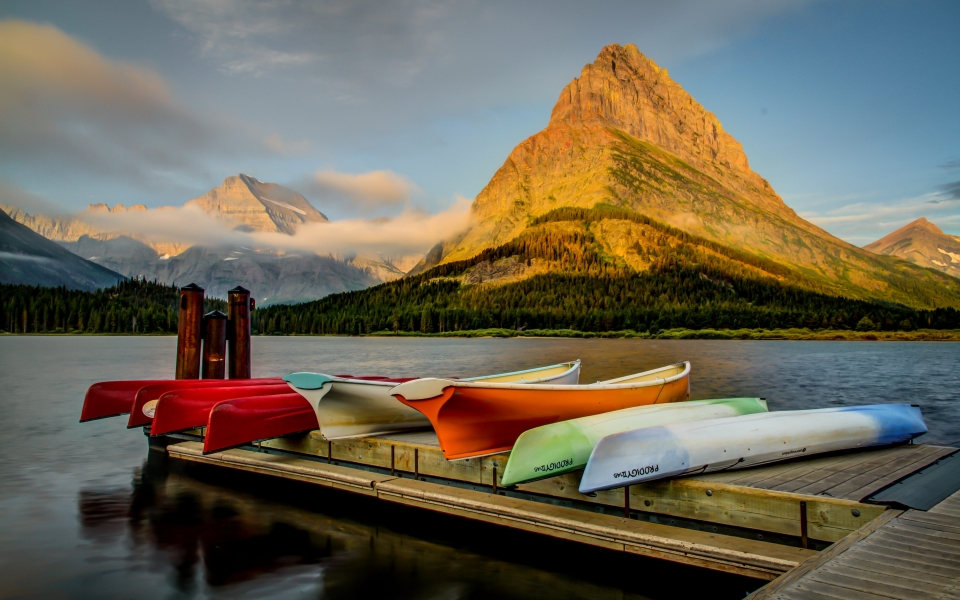 Colorful kayaks lie on the pier of Swiftcurrent Lake as the sunrise illuminates the mountain.
