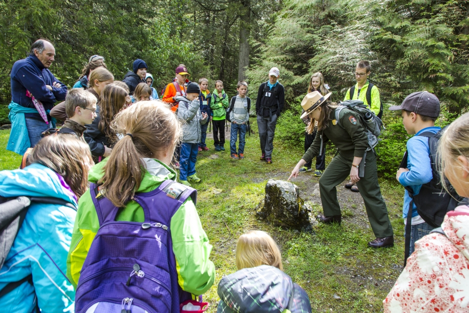 A group of elementary school students in a circle around a park ranger pointing at a rock at Glacier National Park