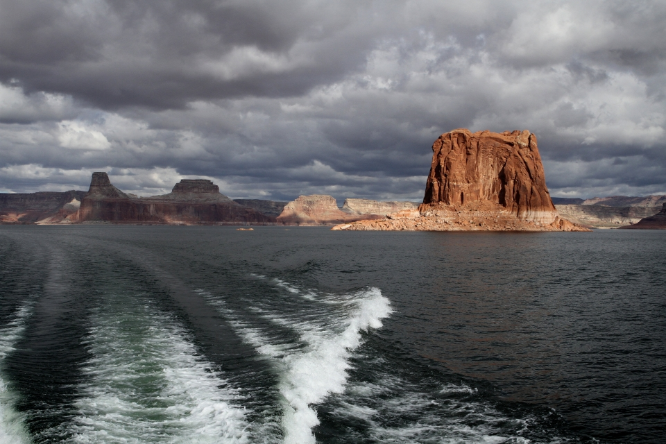 Wake of a boat on Lake Powell with red sandstone cliffs in the horizon at Glen Canyon National Recreation Area