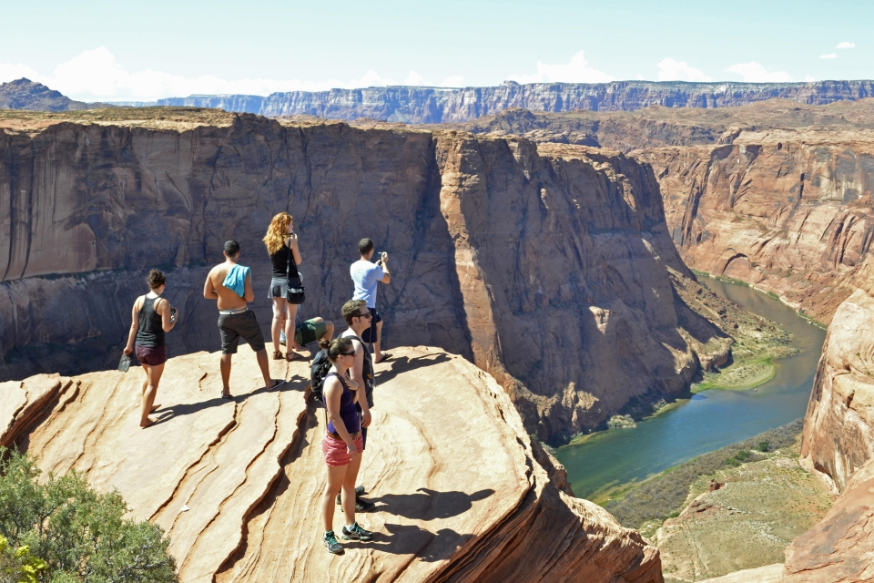 Seven people on the rocky overlook into the canyon at Horseshoe Overlook at Glen Canyon National Recreation Area