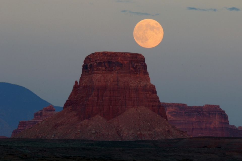 An orange moon stands just above the Tower Butte of Glen Canyon National Recreation Area