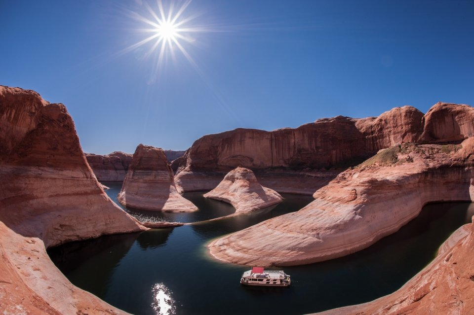 The bright sun in a blue sky over the river and the red Reflection Canyon of Glen Canyon