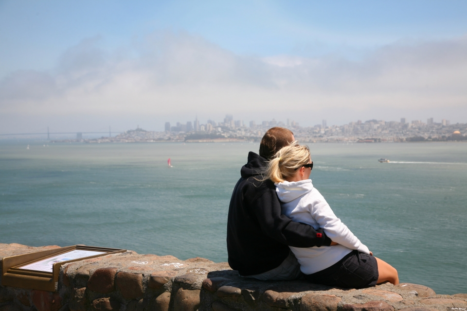 Male and female couple cuddling on wall looking out to the San Francisco Bay