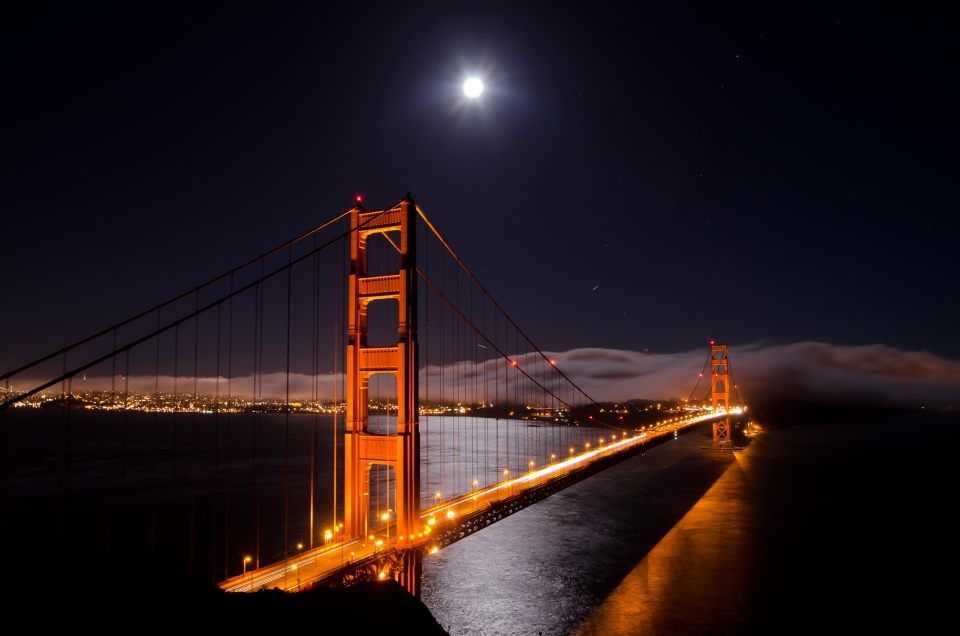 The moon shines brightly over the orange lit Golden Gate Bridge with distant clouds hovering just above the waters.