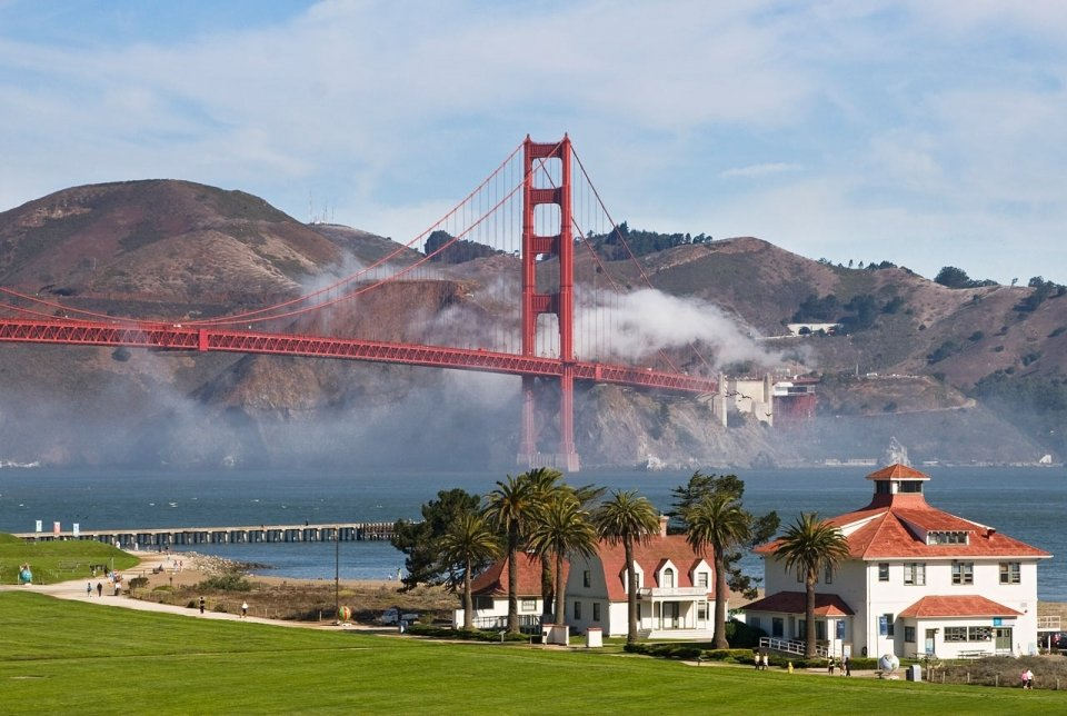 Fog wafts over the Marin side of the Golden Gate Bridge with the Presidio below