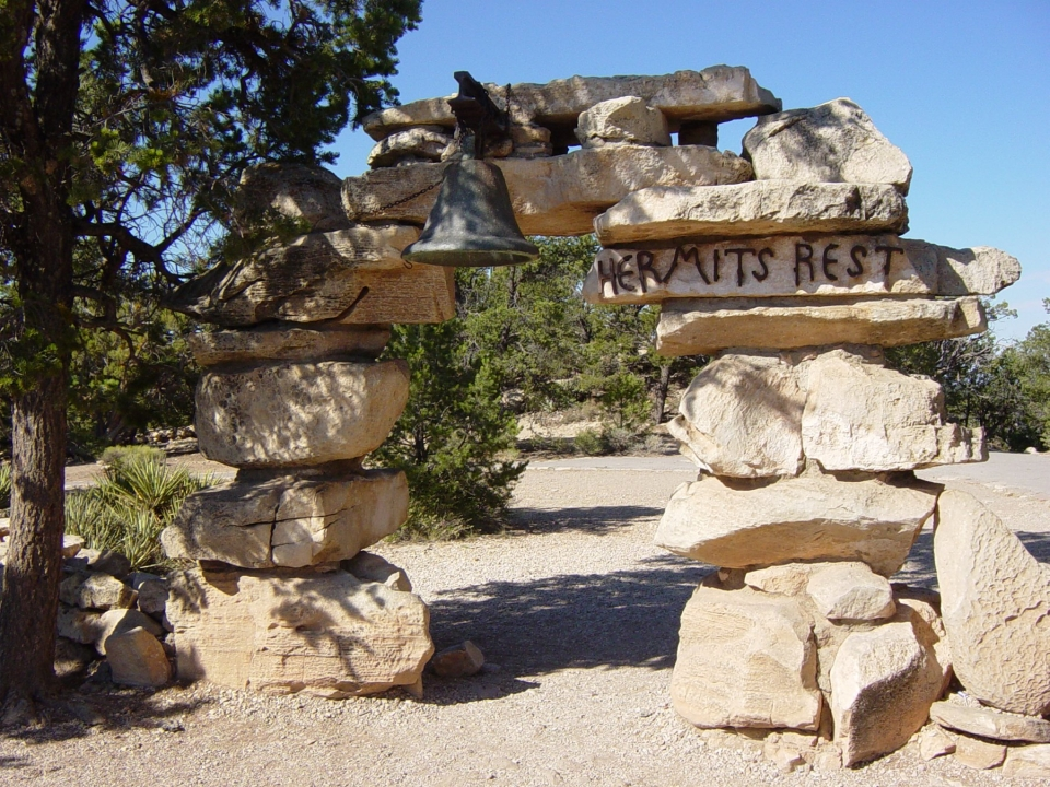 """Stone arch with bell with a """"Hermit's Rest"""" sign at Grand Canyon National Park"""
