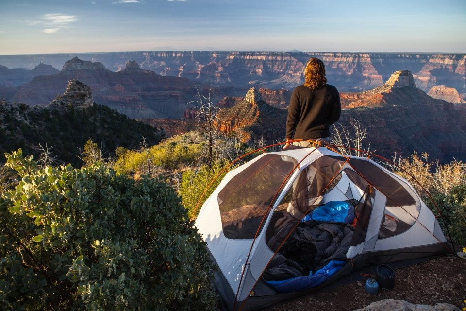 A person standing next to a tent watching Grand Canyon National Park light up during sunrise